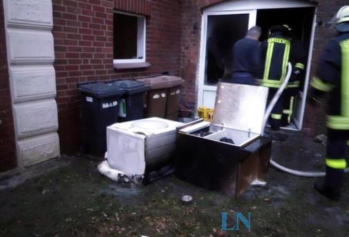 Einen Wäschetrockner und einen Schuhschrank trugen die Feuerwehrmänner nach draußen. Das Feuer hatten Nachbarn bereits mit einem Feuerlöscher erstickt.